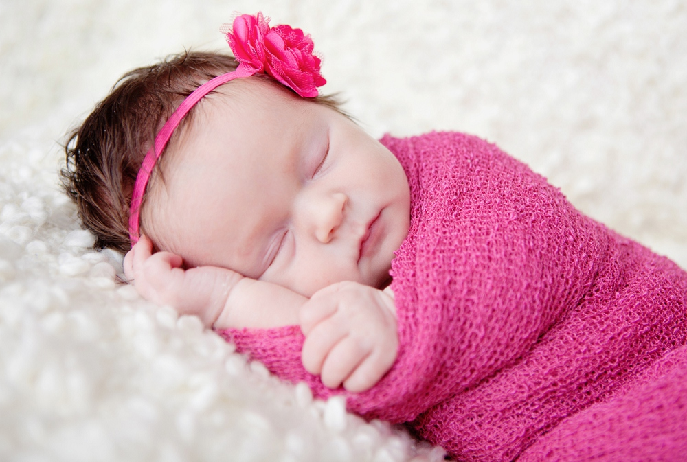 Newborn photographer orpington baby swaddled in pink wrap